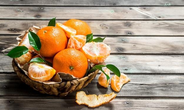 Mandarini succosi con foglie in basret. sullo sfondo di legno