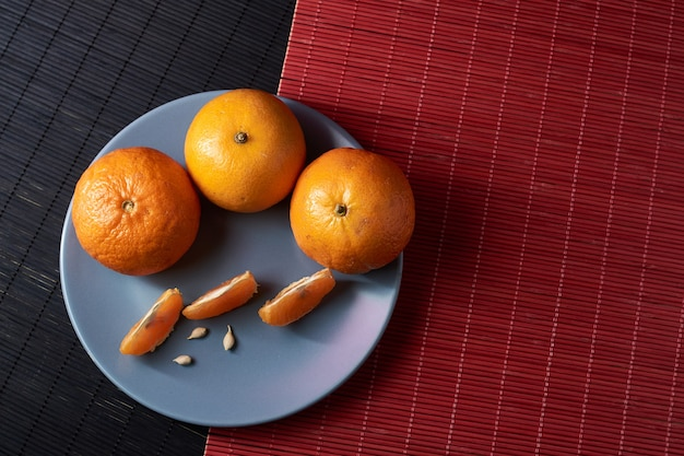 Mandarini arancioni succosi e fette nel piatto su un tavolo in stile nero con rosso