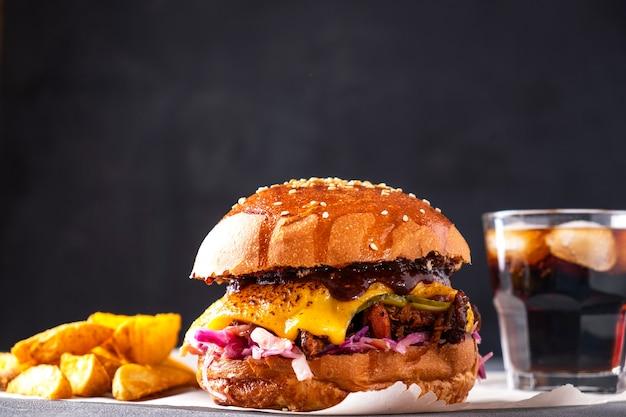 Hamburger di maiale stirato succoso servito con patatine fritte e soda. cibo di strada