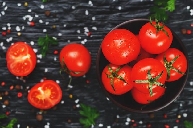 Pomodorini rossi succosi con spezie, sale grosso e verdure. pomodori dolci e maturi per insalate e come ingredienti per cucinare