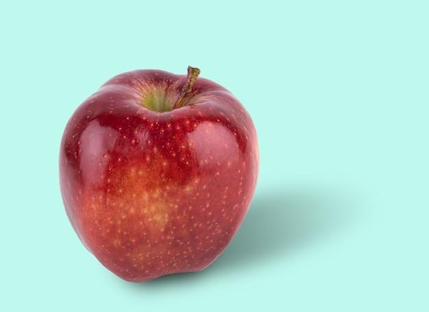 Succosa mela rossa deliziosa su sfondo azzurro. vista frontale e copia spazio.