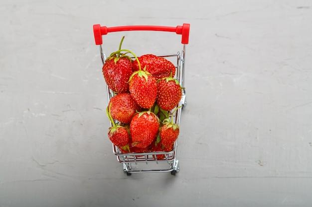 Succose fragole mature in un carrello della spesa su uno sfondo grigio.