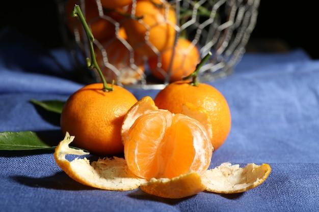 Mandarini maturi succosi con foglie sulla tovaglia