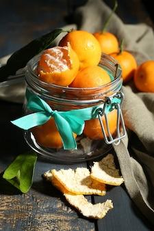 Mandarini maturi succosi con le foglie sulla tavola di legno