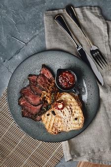 Succoso arrosto di manzo con ciabatta in salsa di pomodoro è splendidamente affettato e disposto su piatti vista dall'alto bella tavola apparecchiata bella che serve cibo tradizionale italiano sfondo grigio