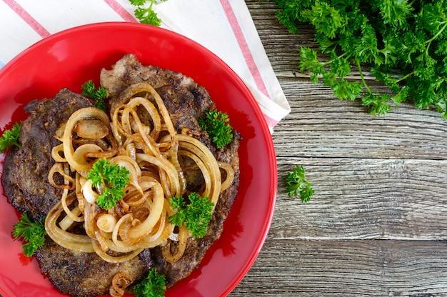 Fette succose di fegato e cipolle fritte su un piatto rosso. vista dall'alto.