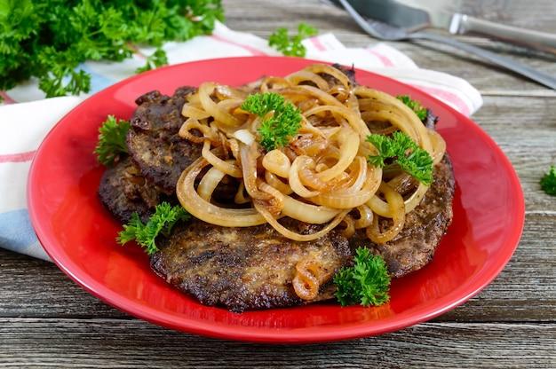 Fette succose di fegato e cipolle fritte su un piatto rosso.