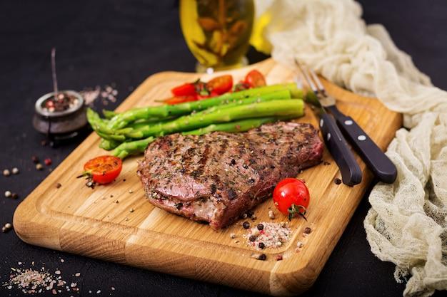 Succosa bistecca di manzo raro con spezie su una tavola di legno e contorno di asparagi.