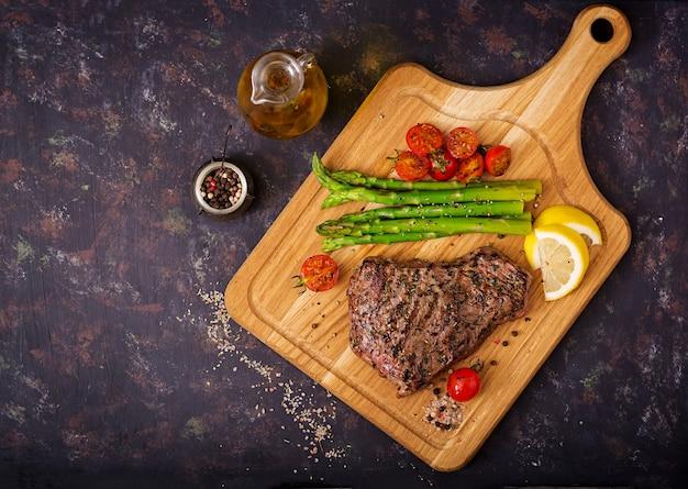 Manzo raro bistecca succosa con spezie su una tavola di legno e contorno di asparagi.