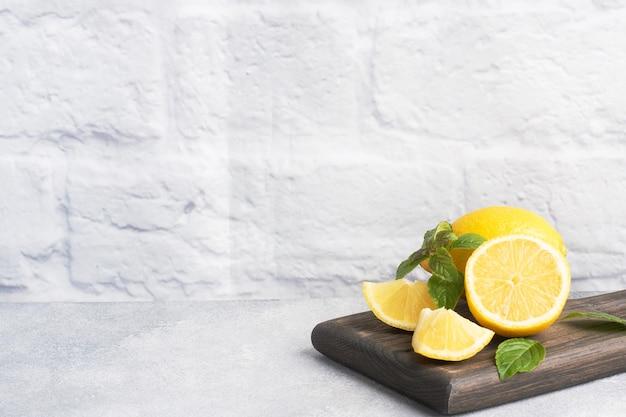 Succosi limoni gialli interi e tagliati con foglioline di menta fresca