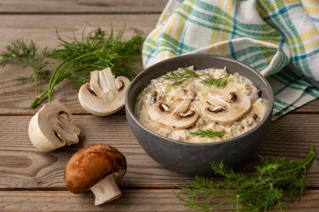 Julienne con funghi prataioli, funghi ed erbe aromatiche su un tavolo di legno
