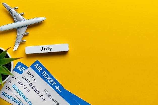 Concetto di viaggio di luglio con l'aeroplano e biglietti su giallo con lo spazio della copia