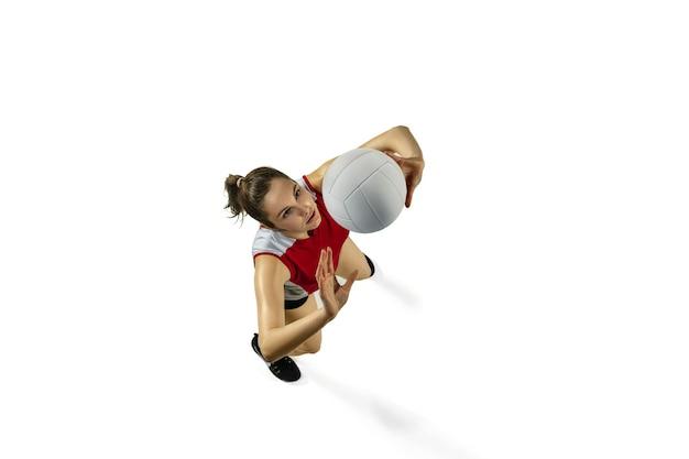 In salto e in volo. giovane giocatore di pallavolo femminile isolato su sfondo bianco per studio. donna in abbigliamento sportivo e scarpe da ginnastica che si allenano, giocando. concetto di sport, stile di vita sano, movimento e movimento.