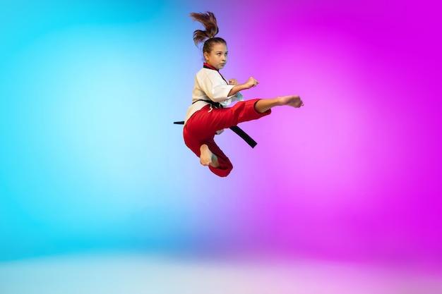 Nel salto. karate, ragazza di taekwondo con cintura nera isolata su sfondo sfumato in luce al neon. piccola modella caucasica, allenamento sportivo per bambini in movimento e azione. sport, movimento, concetto di infanzia.