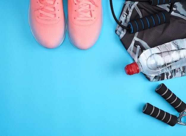 Corda per saltare, bottiglia d'acqua, scarpe da ginnastica rosa, vestiti per lo sport e il fitness
