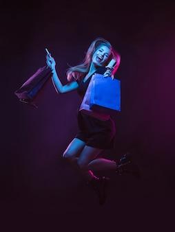 Saltare, volare in alto con le borse della spesa, ridere. ritratto di giovane donna in luce al neon su sfondo scuro. le emozioni umane, venerdì nero, lunedì cibernetico, acquisti, vendite, concetto di finanza.