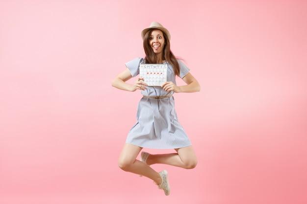 Saltando felice divertente donna in abito blu, cappello che tiene il calendario dei periodi per controllare i giorni delle mestruazioni isolati su sfondo rosa di tendenza brillante. concetto medico, sanitario, ginecologico. copia spazio.