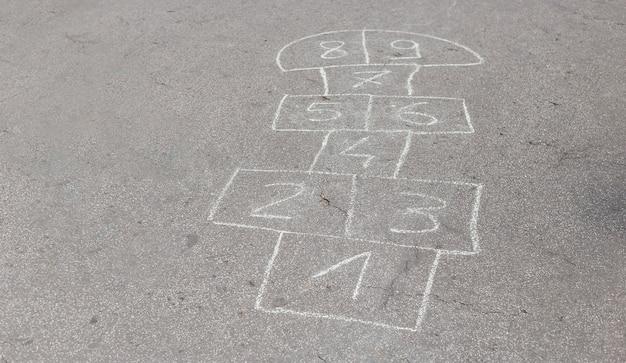 Gioco della campana di salto con i numeri all'aperto in una giornata di sole. attività estive per bambini.