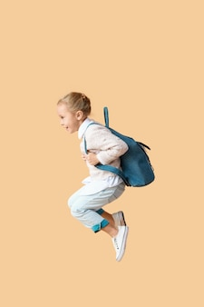 Saltando la piccola studentessa sul beige