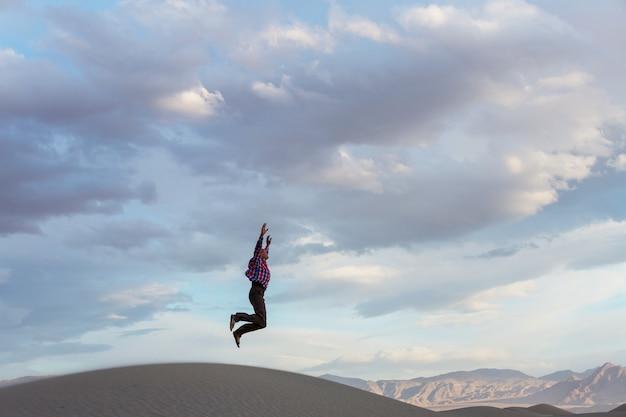 Uomo che salta in dune di sabbia al tramonto