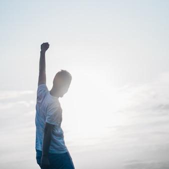 Uomo che salta. il giovane pazzo sta saltando sulla vetta rocciosa sopra il paesaggio. sagoma di uomo che salta e cielo al tramonto. elemento di design. effetto vintage.