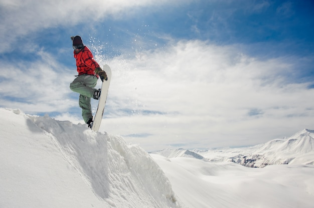 Snowboarder di salto che tiene la mano sullo snowboard