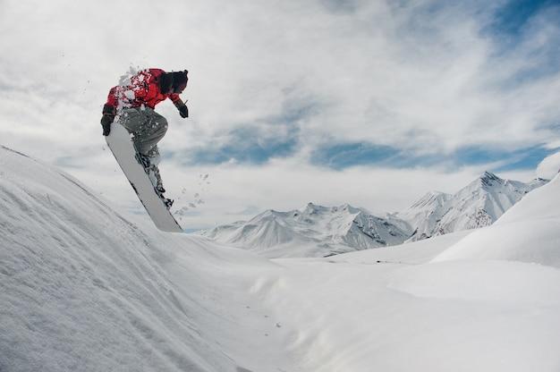 Snowboarder di salto che tiene la sua mano sullo snowboard