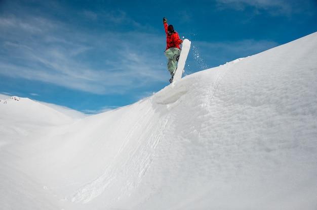 Snowboarder di salto che tiene una mano sullo snowboard