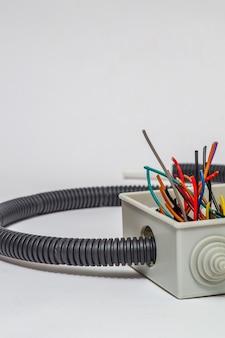 Scatola di giunzione con fili per riparare l'impianto elettrico in casa o in ufficio su sfondo grigio