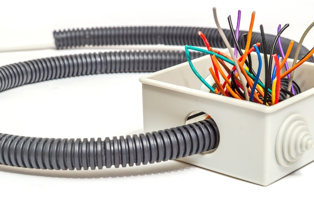 Scatola di giunzione con fili per riparare l'impianto elettrico in casa o in ufficio su sfondo bianco