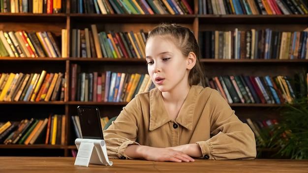 Giovane studentessa parla seduta alla scrivania con lo smartphone