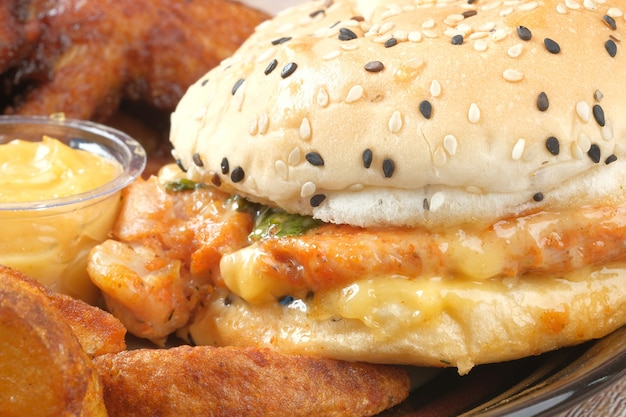 Concetto di cibo spazzatura con hamburger e costolette di patate sulla piastra