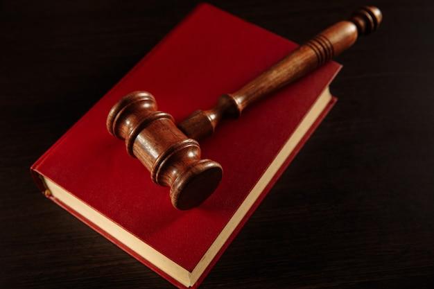 Biblioteca giuridica sul tavolo. martelletto e libri di legno.