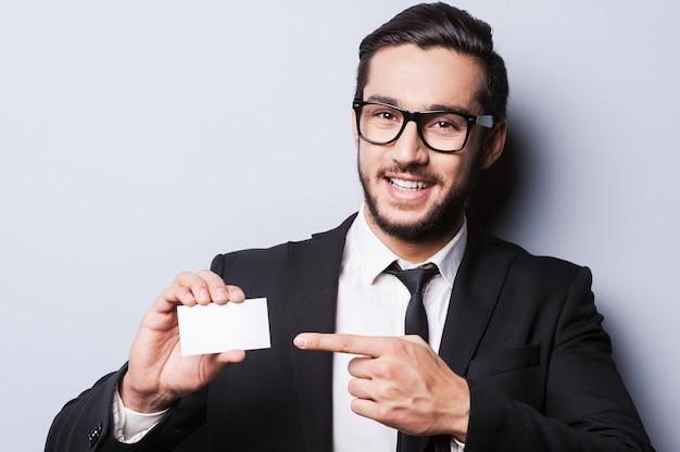 Solo tutto questo numero! bel giovane in abiti da cerimonia che allunga un biglietto da visita mentre si trova su uno sfondo grigio