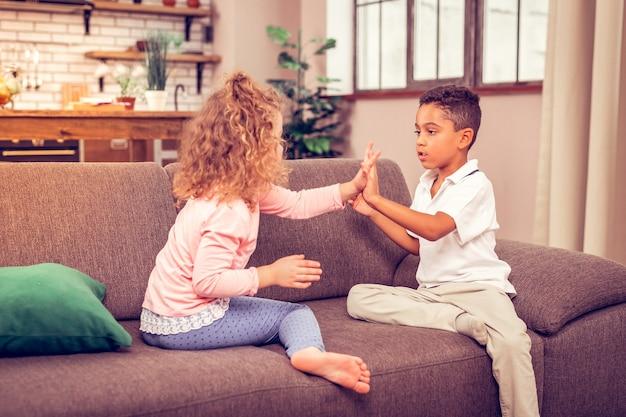 Solo attenzione. ragazzo bruno concentrato seduto di fronte al suo amico mentre trascorre i fine settimana a casa home