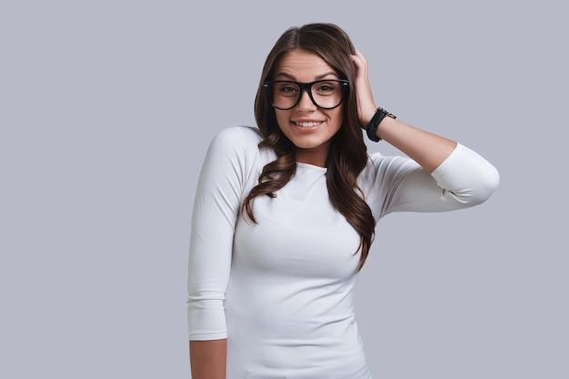 Semplicemente essere se stessa. bella giovane donna che tiene la mano tra i capelli e sorride mentre sta in piedi su uno sfondo grigio