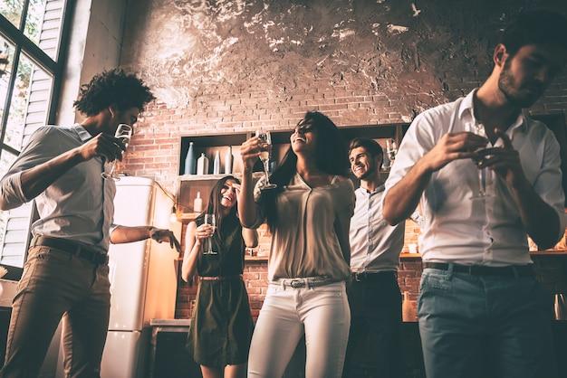 Balla e basta! inquadratura dal basso di giovani allegri che ballano e bevono mentre si godono la festa a casa in cucina