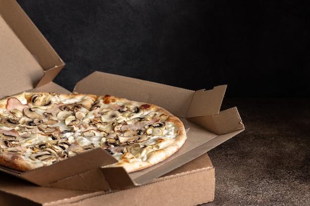 Pizza appena consegnata in scatola di cartone, pizza a fette con prosciutto e funghi, messa a fuoco selettiva