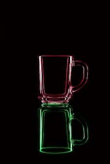 Solo un bicchiere su uno sfondo nero con un riflesso. rosso e verde. isolato.