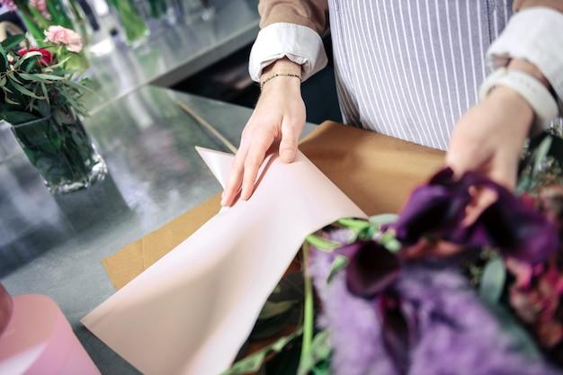 Guarda. primo piano di mani maschili che toccano i fiori, compongono il bouquet