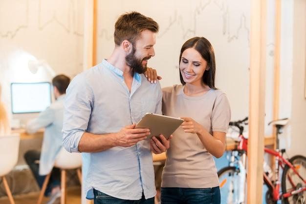 Guarda questo! allegro giovane uomo e donna che discutono di qualcosa e guardano insieme la tavoletta digitale mentre i loro colleghi lavorano in background