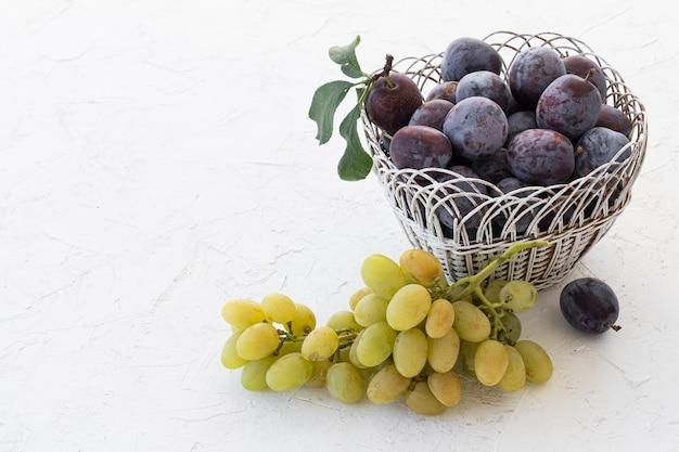 Prugne mature appena raccolte in cesto di vimini e un grappolo di uva bianca matura sullo sfondo bianco strutturato. frutti appena raccolti. vista dall'alto.