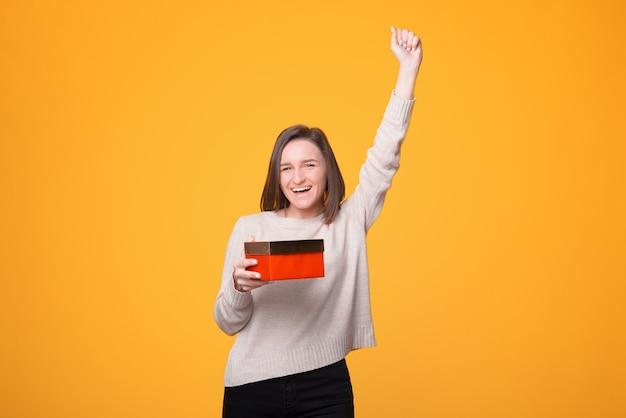 Appena ricevuto il regalo di natale, giovane donna stupita che celebra e tiene in mano la confezione regalo