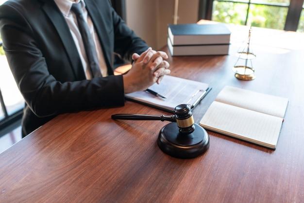 Concetto di giustizia un giudice onorevole seduto al centro del grande tavolo di legno con il martello giudicante e la bilancia che sembrano potenti.