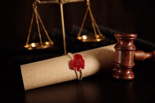 Martelletto della giustizia e ultima volontà e documento del testamento sulla tavola di legno.