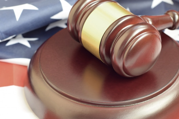 Maglio della giustizia sulla bandiera degli stati uniti in un'aula di tribunale durante un processo giudiziario