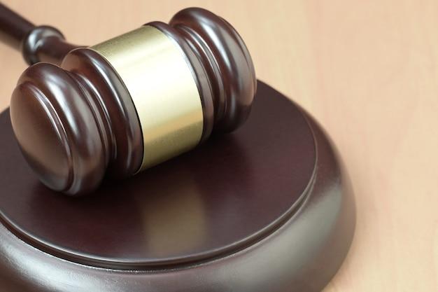 Maglio di giustizia sulla scrivania di legno in un'aula di tribunale durante un processo giudiziario. concetto di diritto e spazio vuoto per il testo. martello del giudice