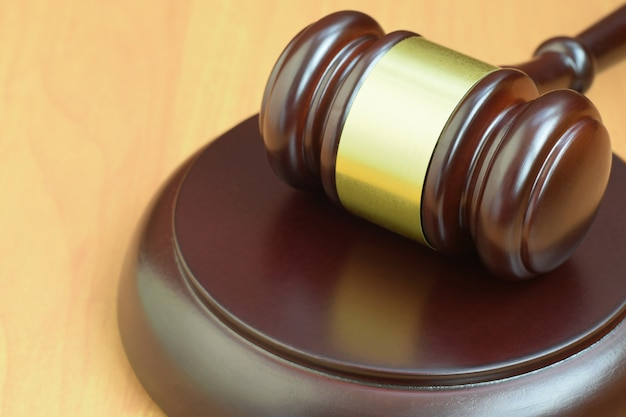 Maglio della giustizia sullo scrittorio di legno in un'aula di tribunale durante un processo giudiziario