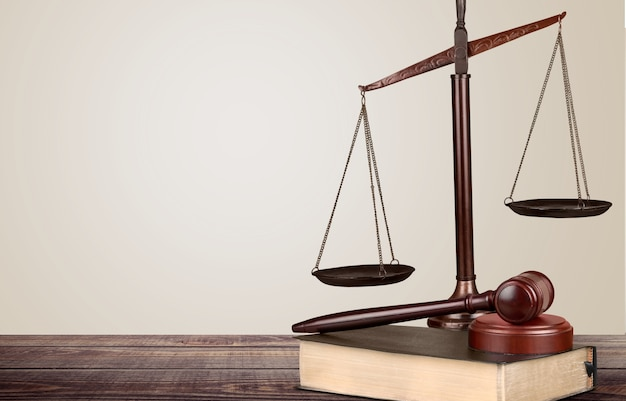 Bilancia della giustizia e libro e martelletto di legno sul tavolo. concetto di giustizia
