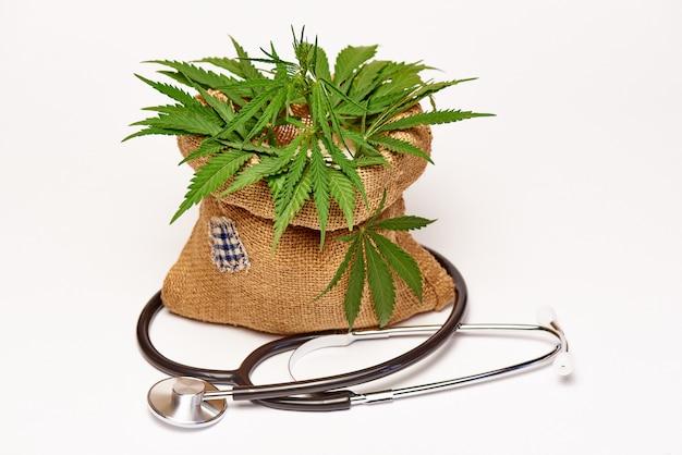 Borsa di iuta con cannabis e uno stetoscopio su uno spazio bianco.